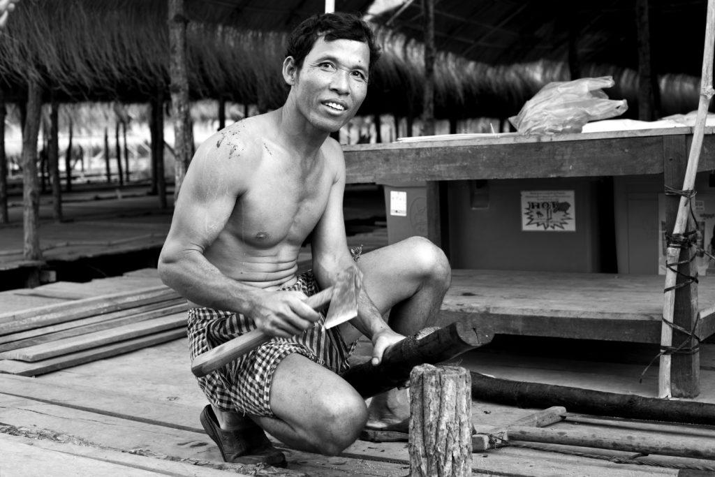 Homme coupant du bois à Kompi, Cambodge : .