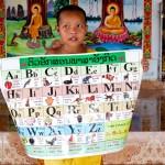 jeune moine tenant une affiche avec l'alphabet laos