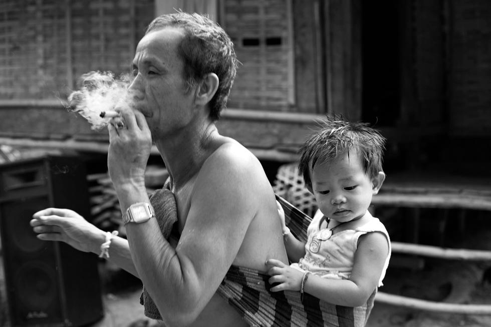 grand père a la cigarette avec son petit fils dans le dos mong noi laos