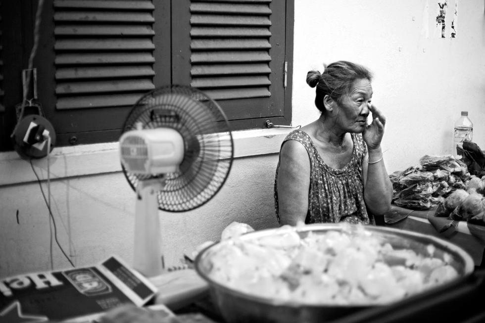 vieille dame à coté d'un ventilateur luang prabang laos